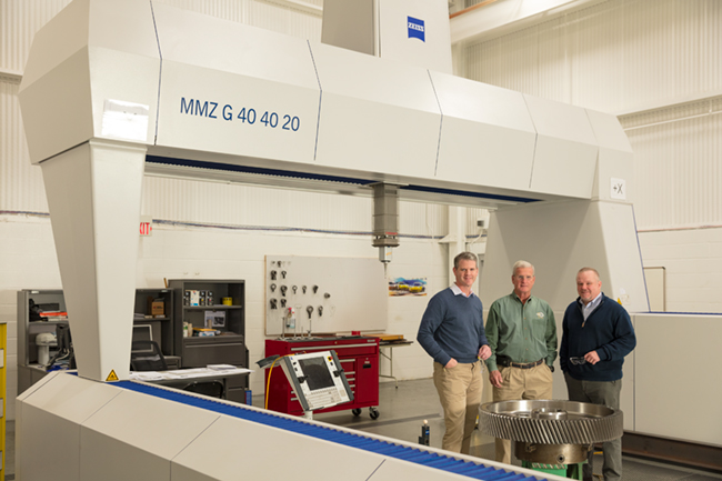 A group of three Horsburgh & Scott employees standing near a precision coordinated measuring machine.