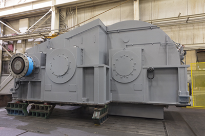 A large, grey-colored, industrial gearbox used in heavy-duty steel applications.