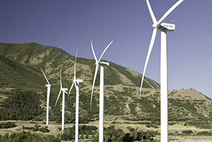 Five large, white windmills near mountains.