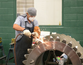 A person wearing a blue apron and face mask grinding an industrial gear.