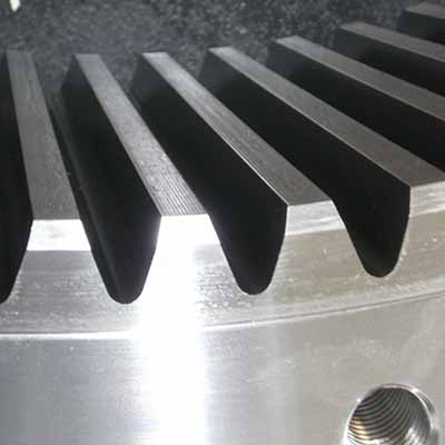 The side view of the teeth on a large, shiny, heavy-duty internal gear.
