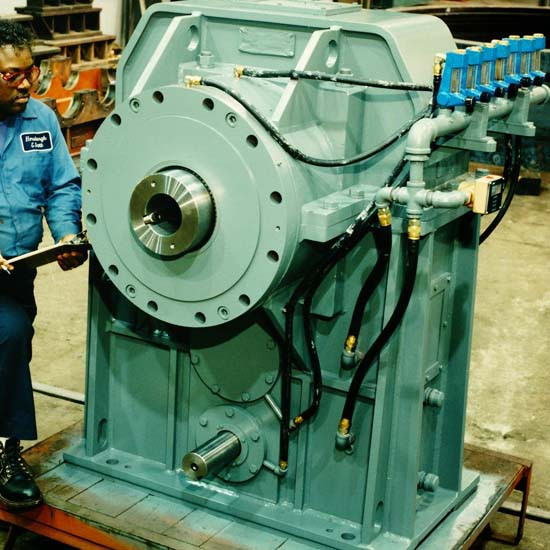 A man wearing a blue shirt and blue pants standing near a gearbox used for extruding.