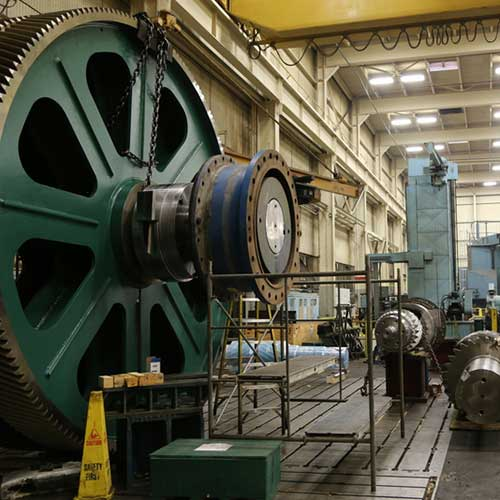 A large, green-colored industrial gear.