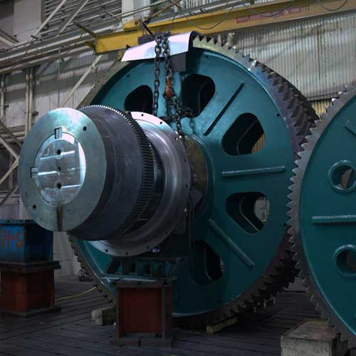 Two large, green-colored, industrial gears.