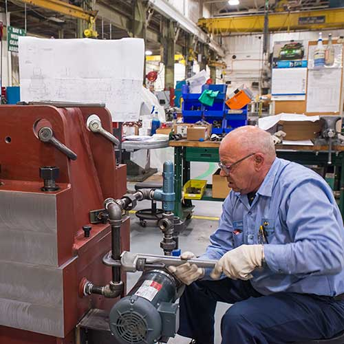 A man wearing a blue shirt and blue pants sitting on a stool repairing a red-colored, industrial gearbox.